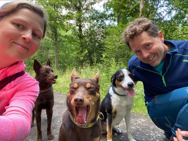 en kvinna, en man och tre hundar